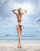 Young, beautiful, sporty and sexy blond woman relaxing on the beach — Stock Photo