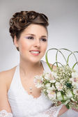 Young and beautiful bride standing with the flower bouquet — Stock Photo