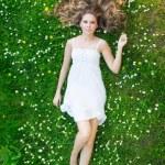 ung, frisk och vacker flicka liggande i gräset — Stockfoto