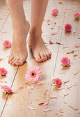 Spa compositions of sexy female legs and plenty of different petals and flowers — Stock Photo