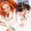 A happy mother and a little daughter drawing with markers — Stockfoto