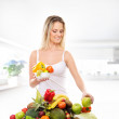Young attractive girl with a pile of fruits and vegetables isola — Stock Photo