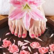 Spa background with a beautiful legs, flowers, petals and cerami — Stock Photo