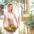 Attractive woman with a basket full of fruits — Stock Photo #29158851