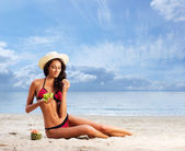 Beautiful woman in swimsuit relaxing on a beach — Stock Photo