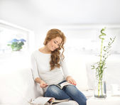 Young beautiful woman reading magazine on the sofa — Stock Photo