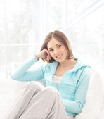 Young, attractive, happy woman sitting in the bed over white bac — Stock Photo