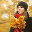 Young and beautiful girl walking in bright and colorful autumn park — Stockfoto