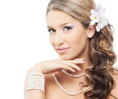 Young and attractive lady with a pearl jewelry and a flower in her hair — Stock Photo