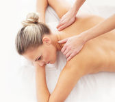 Young attractive woman getting massaging treatment over white ba — Stock Photo