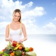 Girl with a pile of fruits and vegetables — Stock Photo