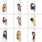 Set of teenagers with a giant white billboard — Stock Photo