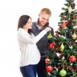 A pregnant woman and a happy man posing near the Christmas tree — Stock Photo #35959173