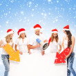 A group of teenagers in Christmas hats pointing on a blank banne — Photo