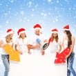 A group of teenagers in Christmas hats pointing on a blank banne — Stock Photo
