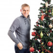 Stock Photo: A pregnant woman and a happy man posing near the Christmas tree
