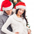 A pregnant woman and a happy man posing near the Christmas tree — Stock Photo