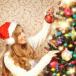 Beautiful teenager girl decorating the Christmas tree — Stock Photo #35959405