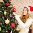 Beautiful teenager girl decorating the Christmas tree — Stock Photo #35959419