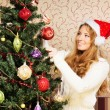 Beautiful teenager girl decorating the Christmas tree — Stock Photo