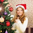 Beautiful teenager girl decorating the Christmas tree — Stock Photo #35959433