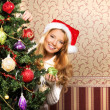 Beautiful teenager girl decorating the Christmas tree — Stock Photo #35959441