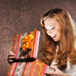 A happy teenage girl opening a Christmas present — Photo