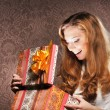 A happy teenage girl opening a Christmas present — Stok fotoğraf