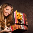 A young and happy teenage girl opening the present — Foto de Stock