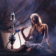 A young blond woman in sexy lingerie smoking a hookah — Stock Photo