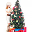 A happy woman decorating the Christmas tree on white — Stock Photo