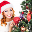 A happy woman decorating the Christmas tree on white — Stok fotoğraf