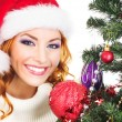 A happy woman decorating the Christmas tree on white — Stock Photo #35959955