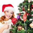 A happy woman decorating the Christmas tree on white — Stock Photo #35959959