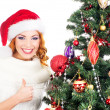 A happy woman decorating the Christmas tree on white — Stock Photo #35959971