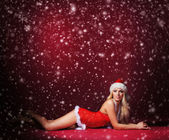 Young sexy Santa in lingerie over red background — Stock Photo