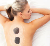 Young attractive woman getting hot stone treatment over white ba — Stock Photo
