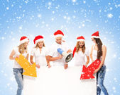 A group of teenagers in Christmas hats pointing on a blank banne — Stok fotoğraf