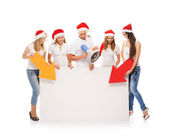 A group of teenagers in Christmas hats pointing on a blank banne — 图库照片