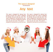 A group of teenagers in Christmas hats pointing on a blank banne — Стоковое фото