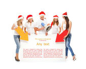A group of teenagers in Christmas hats pointing on a blank banne — Foto Stock