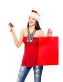 A happy woman in a Christmas hat holding a red shopping bag — Stock Photo