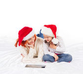 A happy mother and a daughter relaxing in red Christmas hats — Stock Photo