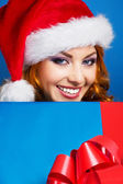 A happy woman in a red Christmas hat on a blue background — Stock Photo