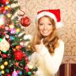 Beautiful teenager girl decorating the Christmas tree — Stock Photo