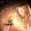 A happy teenage girl opening a Christmas present — ストック写真