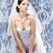 Stock Photo: Young sexy bride in erotic lingerie over blue