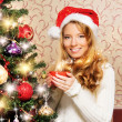 Beautiful teenager girl decorating the Christmas tree — Stock Photo #35960225