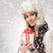 A young woman in a winter hat holding a Christmas present — Stock Photo #35960511