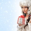 A young woman in a winter hat holding a Christmas present — Stock Photo